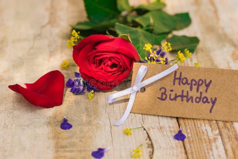 Χρόνια πολλά ευχετήρια κάρτα με το κόκκινο ροδαλό λουλούδι στοκ εικόνες