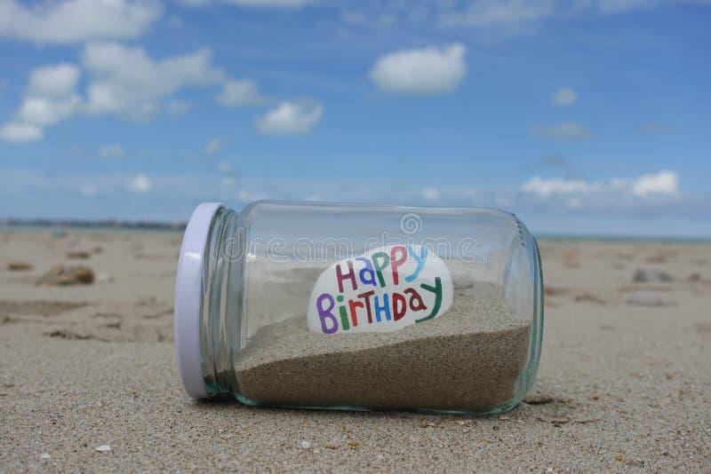 Χρόνια πολλά σε μια πέτρα σε ένα βάζο γυαλιού με την άμμο πέρα από την παραλία στοκ εικόνες με δικαίωμα ελεύθερης χρήσης