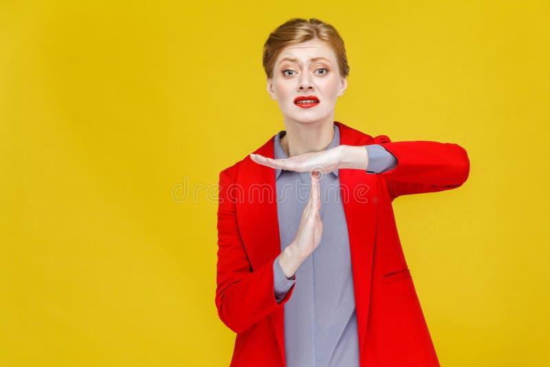 Χρόνος έξω! Δυστυχισμένη επιχειρησιακή γυναίκα στο κόκκινο κοστούμι που παρουσιάζει σημάδι μικρής διακοπής στοκ εικόνες