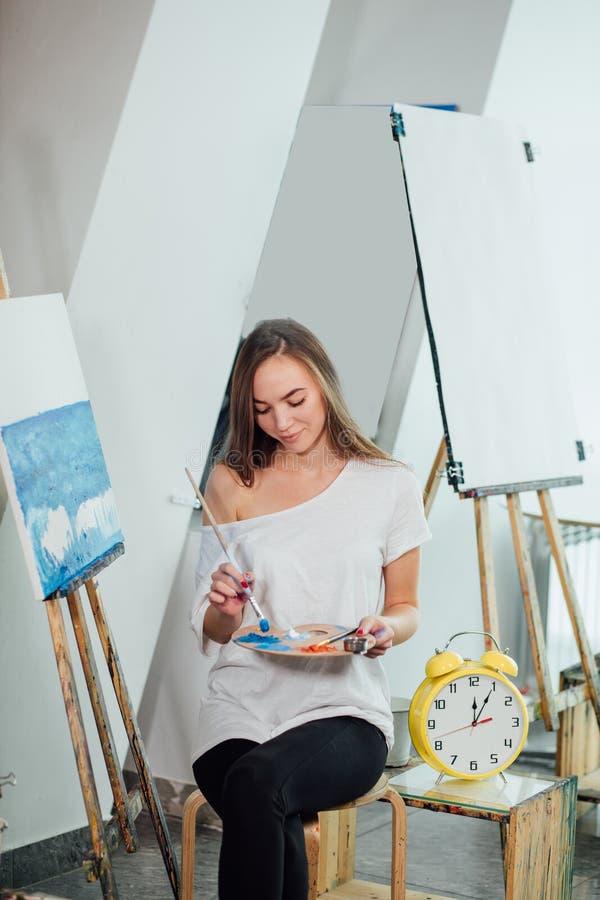 Χρόνος για τη δημιουργία Ελκυστική γυναίκα που θέτει fullface χρωματίζοντας sea-scape στοκ εικόνες