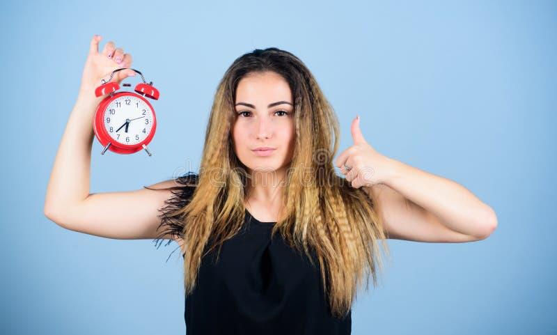 Χρόνος εργασίας ζώνη ώρας ακρίβεια και πειθαρχία κορίτσι που κρατά ξυπνητήρι καθεστώς πρόωρη αφύπνιση κουδούνι χτυπάει στοκ φωτογραφίες