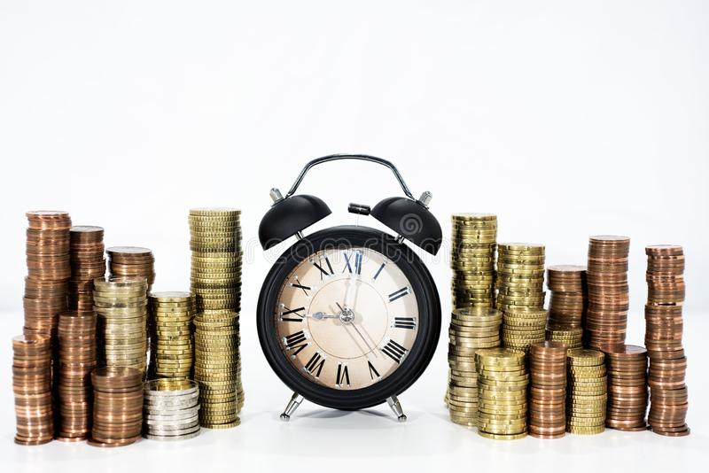 Χρόνος και αφαίρεση χρημάτων Πολλά νομίσματα με το κομψό μαύρο ρολόι στοκ εικόνα