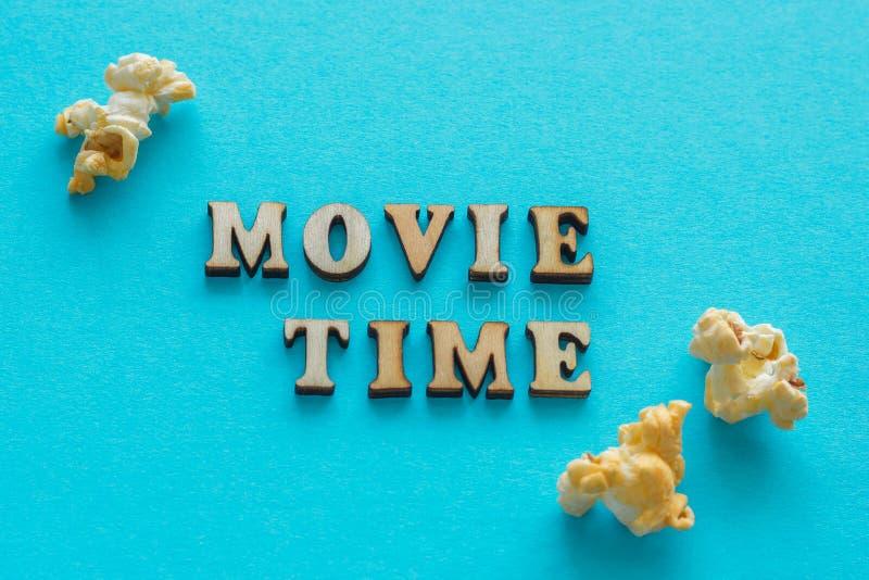 Χρόνος ` κινηματογράφων κειμένων ` και popcorn στο μπλε υπόβαθρο στοκ φωτογραφία με δικαίωμα ελεύθερης χρήσης