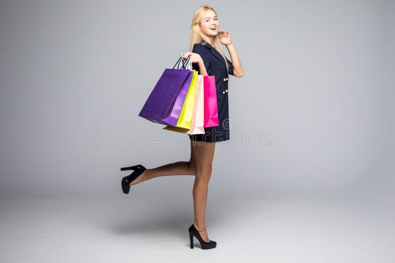 Χρόνος να αγοραστούν τα νέα φορέματα Η όμορφη νέα γυναίκα στο όμορφο φόρεμα που εξετάζει τη κάμερα και που κρατά τις αγορές τοποθ στοκ εικόνα με δικαίωμα ελεύθερης χρήσης