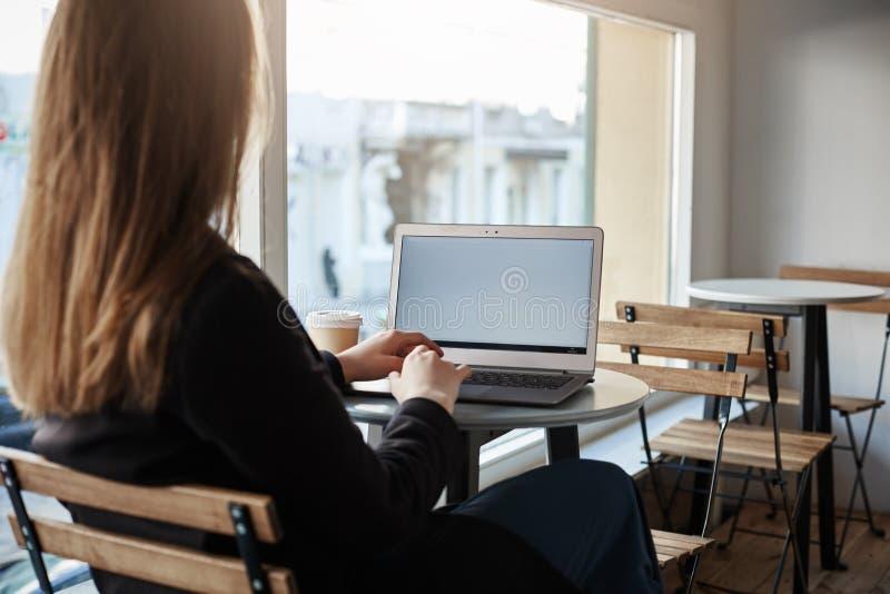 Χρόνος να είναι παραγωγικός Οπισθοσκόπος του επιτυχούς θηλυκού freelancer στα μοντέρνα ενδύματα που κάθονται στον καφέ λειτουργών στοκ φωτογραφίες