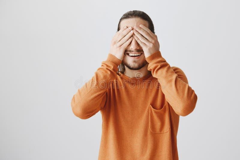 Χρόνος να παραληφθεί η έκπληξη Πορτρέτο της γοητείας του ανυπόμονου ατόμου στο πορτοκαλί πουλόβερ που καλύπτει το όραμα με τους φ στοκ εικόνες