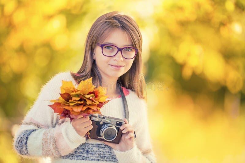 Χρόνος φθινοπώρου Το εφηβικό ελκυστικό χαριτωμένο νέο κορίτσι με την ανθοδέσμη φθινοπώρου και την αναδρομική κάμερα Εποχή φθινοπώ στοκ φωτογραφίες