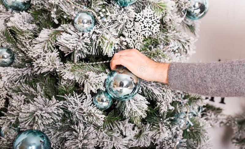 Χρόνος Χριστουγέννων - νέο man& x27 χέρι του s με μια σφαίρα Χριστουγέννων στοκ φωτογραφίες με δικαίωμα ελεύθερης χρήσης
