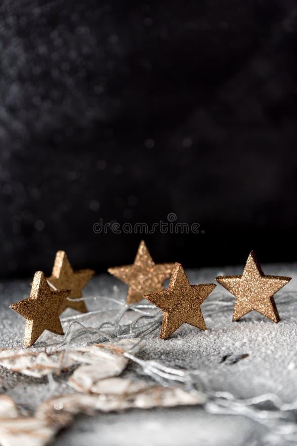 Χρόνος Χριστουγέννων - χρυσά αστέρια στο χιόνι, στο υπόβαθρο μιας σκοτεινής νύχτας στοκ εικόνες