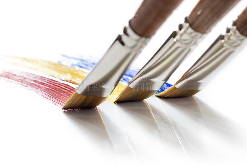χρώματα βουρτσών που χρωματίζουν τρία στοκ εικόνες