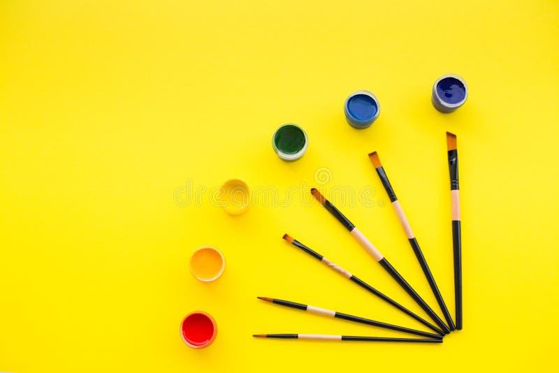 Χρώματα, βούρτσες και κίτρινο υπόβαθρο στοκ φωτογραφία με δικαίωμα ελεύθερης χρήσης