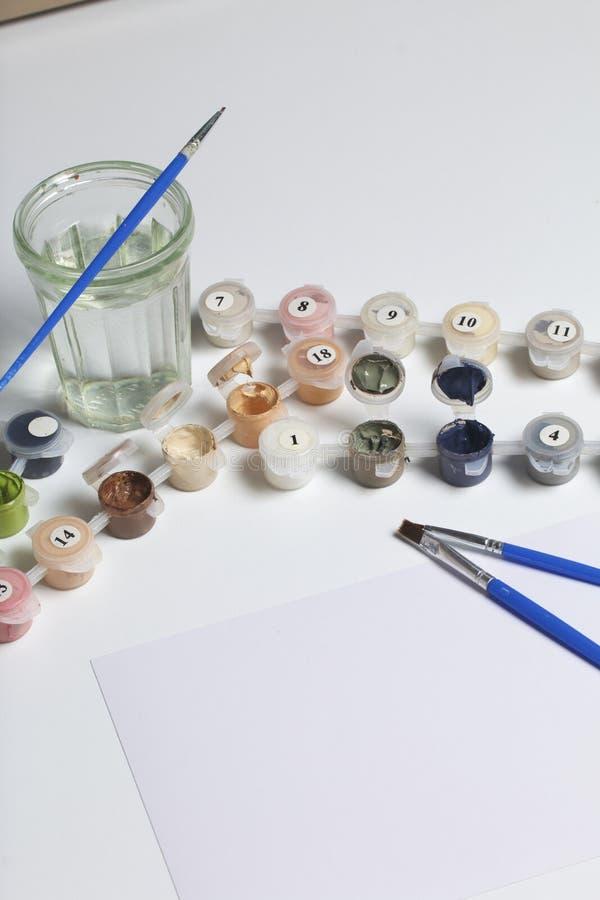 Χρώματα για το σχέδιο από τους αριθμούς Διάφορα εμπορευματοκιβώτια με το χρώμα είναι ανοικτά Δίπλα σε το είναι θύσανοι, ένα φύλλο στοκ φωτογραφίες