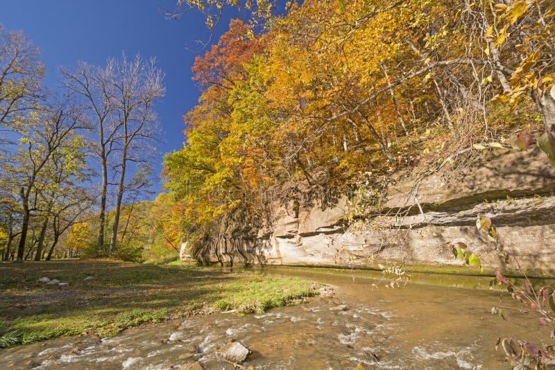 Χρώματα πτώσης και ένας απότομος βράχος ασβεστόλιθων πέρα από ένα ήρεμο ρεύμα στοκ φωτογραφίες