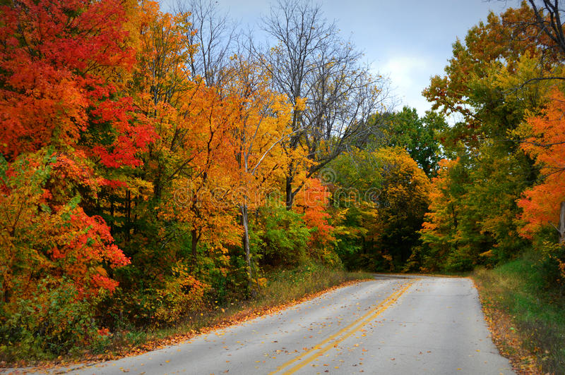 Χρώματα πτώσης, δρόμος με τα κίτρινα λωρίδες στοκ φωτογραφία