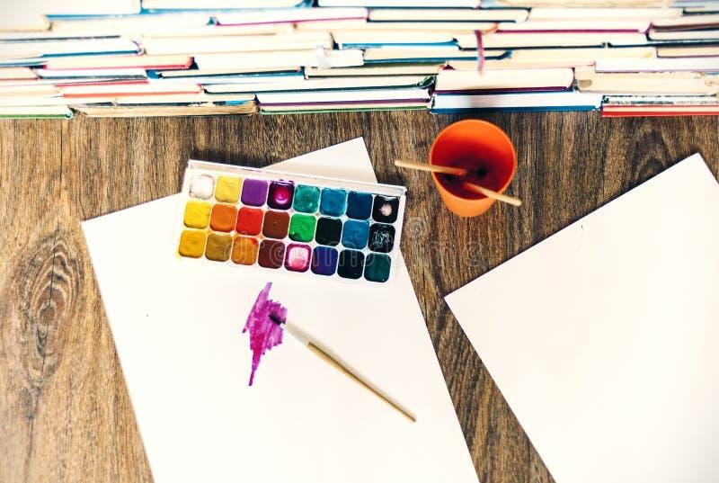 Χρώμα, βούρτσες χρησιμοποιούμενα καλά και φύλλο Watercolor του εγγράφου για τον ξύλινο πίνακα με το σωρό του υποβάθρου βιβλίων στοκ εικόνες με δικαίωμα ελεύθερης χρήσης