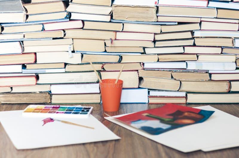 Χρώμα, βούρτσες χρησιμοποιούμενα καλά και φύλλο Watercolor του εγγράφου για τον ξύλινο πίνακα με το σωρό του υποβάθρου βιβλίων στοκ εικόνα με δικαίωμα ελεύθερης χρήσης