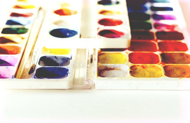Χρώμα και βούρτσες Watercolor που χρησιμοποιούνται καλά στον άσπρο ξύλινο πίνακα με το διάστημα αντιγράφων για το κείμενο στοκ φωτογραφίες