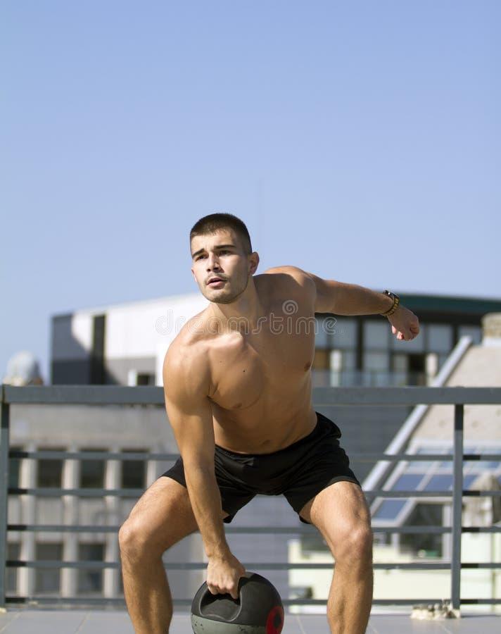 Χτισμένος νέος αθλητικός τύπος Άσκηση με μια σφαίρα ιατρικής πιασιμάτων στοκ εικόνες με δικαίωμα ελεύθερης χρήσης