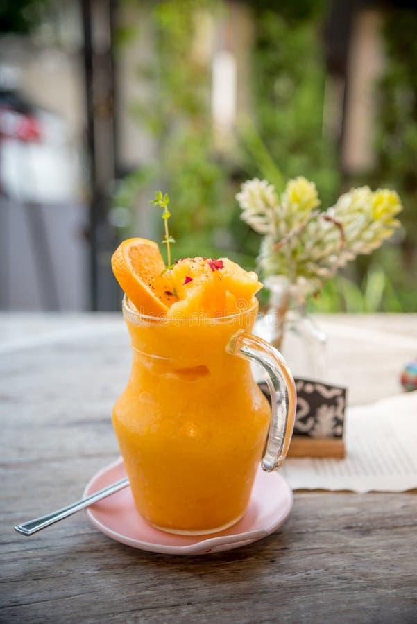 Χυμός από πορτοκάλι που συνδυάζεται σε ένα βάζο ή έναν πορτοκαλή καταφερτζή Decorat γυαλιού στοκ φωτογραφία