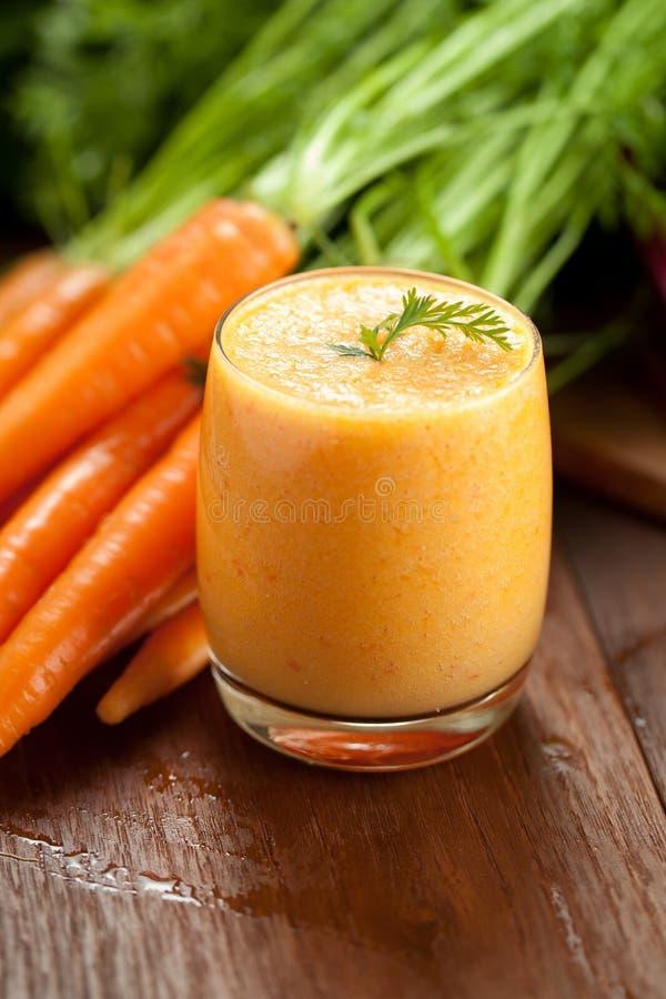 Χυμός καρότων στο γυαλί και φρέσκα υγιή τρόφιμα καρότων σε ένα γκρίζο υπόβαθρο πετρών στοκ φωτογραφία με δικαίωμα ελεύθερης χρήσης