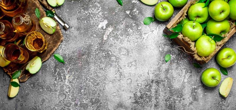 Χυμός της Apple στη στάμνα στην επιτροπή με φρέσκα, πράσινα μήλα στοκ εικόνα