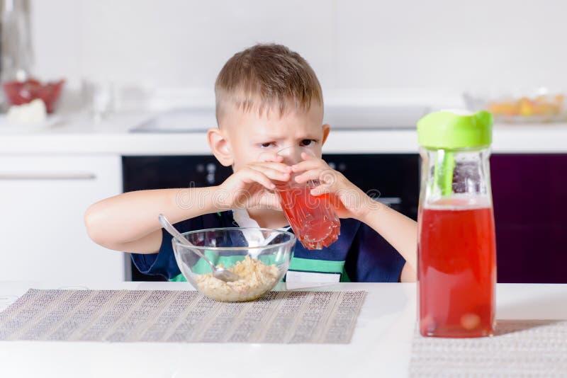 Χυμός φρούτων κατανάλωσης μικρών παιδιών σε μια κουζίνα στοκ εικόνα