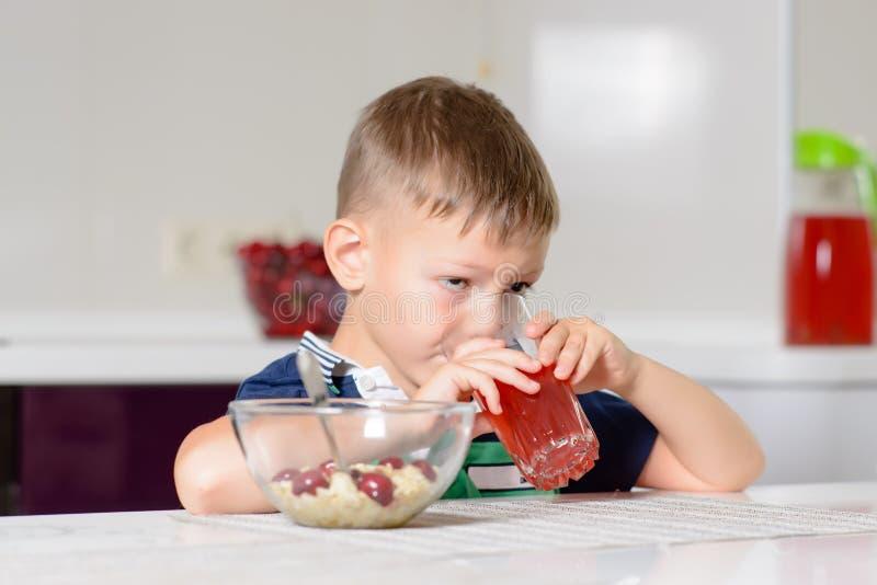Χυμός φρούτων κατανάλωσης μικρών παιδιών σε μια κουζίνα στοκ εικόνες