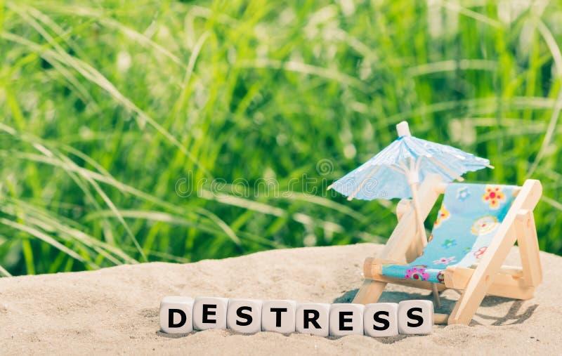 """Χωρίστε σε τετράγωνα τοποθετημένος δίπλα σε μια μορφή καρεκλών παραλιών τη λέξη """"destress """" στοκ φωτογραφίες με δικαίωμα ελεύθερης χρήσης"""