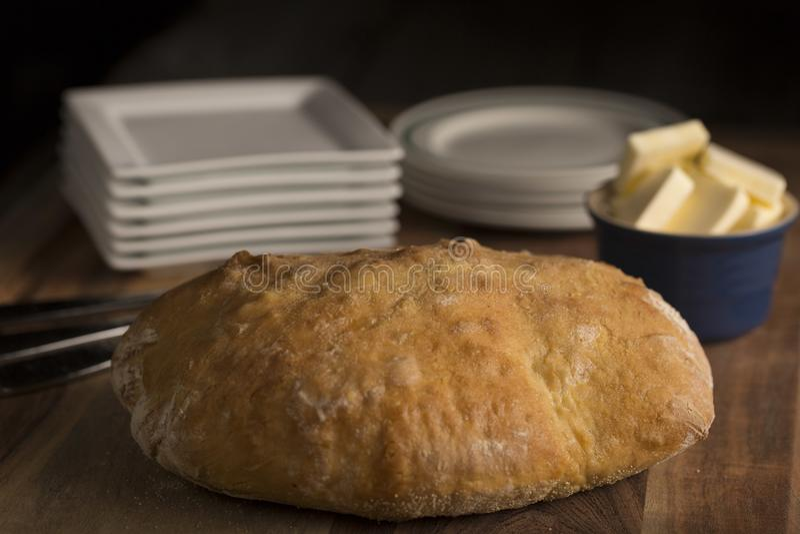 Χωριάτικο ιταλικό ψωμί Pugliese με τα άσπρα πιάτα σε έναν ξύλινο τέμνοντα πίνακα με να σκιάσει στοκ εικόνες με δικαίωμα ελεύθερης χρήσης