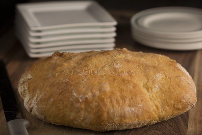 Χωριάτικο ιταλικό ψωμί Pugliese με τα άσπρα πιάτα στοκ φωτογραφία με δικαίωμα ελεύθερης χρήσης