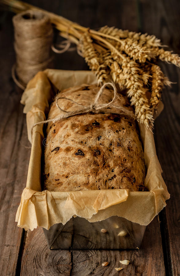 Χωριάτικο ψωμί στον κασσίτερο ψησίματος και σίτος στον εκλεκτής ποιότητας ξύλινο πίνακα στοκ εικόνα με δικαίωμα ελεύθερης χρήσης