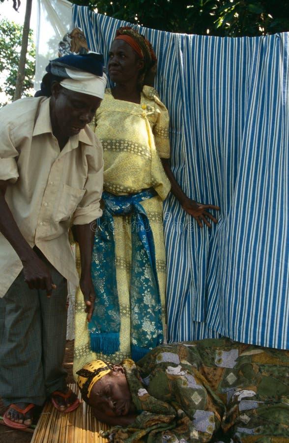 Χωρικοί που βοηθούν μια άρρωστη γυναίκα στην Ουγκάντα στοκ εικόνα με δικαίωμα ελεύθερης χρήσης