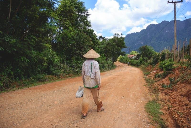 Χωρικός στο Λάος που περπατά κάτω από το βρώμικο δρόμο χωρών στοκ φωτογραφία