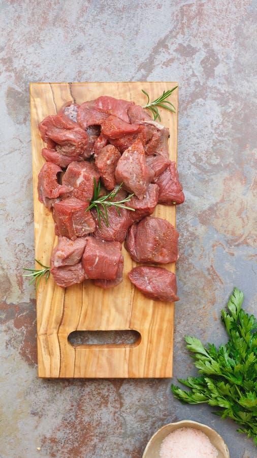 Χωρισμένο σε τετράγωνα ακατέργαστο κρέας με ένα κλαδάκι του δεντρολιβάνου στοκ εικόνες