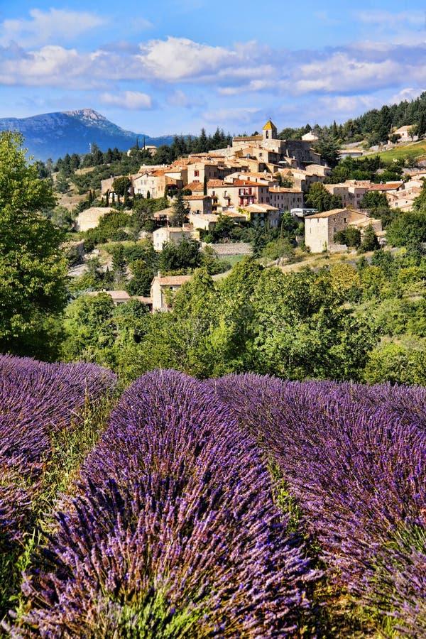 Χωριό κορυφών υψώματος στην Προβηγκία, Γαλλία πίσω από τις σειρές lavender στοκ φωτογραφία