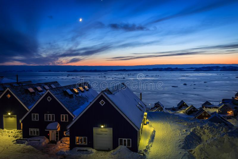 Χωριό στο φιορδ που καλύπτεται στο χιόνι, άποψη ηλιοβασιλέματος με το φεγγάρι, Nuu στοκ εικόνες