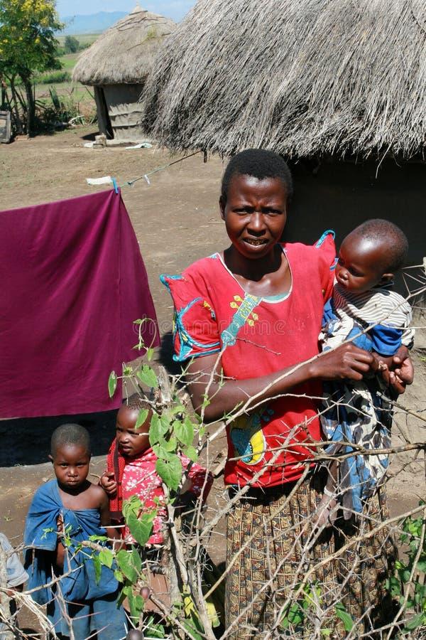 Χωριό Maasai, η αφρικανική οικογένεια που στέκεται κοντά στις καλύβες στοκ εικόνες