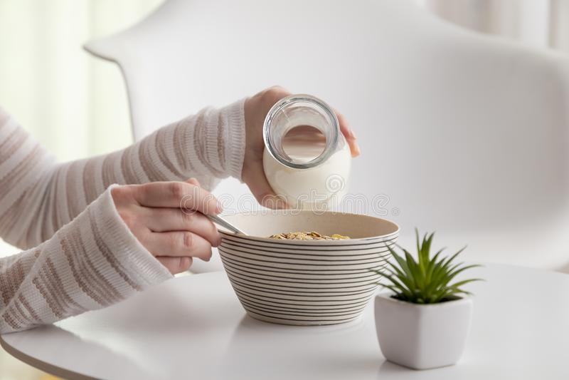 Χύνοντας γάλα γυναικών στο κύπελλο δημητριακών στοκ φωτογραφία