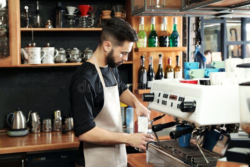 Χύνοντας γάλα Barista στην κανάτα μετάλλων κοντά στη μηχανή καφέ στοκ εικόνες με δικαίωμα ελεύθερης χρήσης