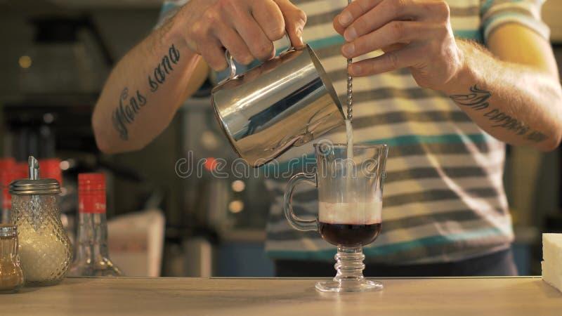Χύνοντας γάλα Barista στο φλυτζάνι γυαλιού καφέ στην καφετέρια κοντά επάνω στοκ εικόνες