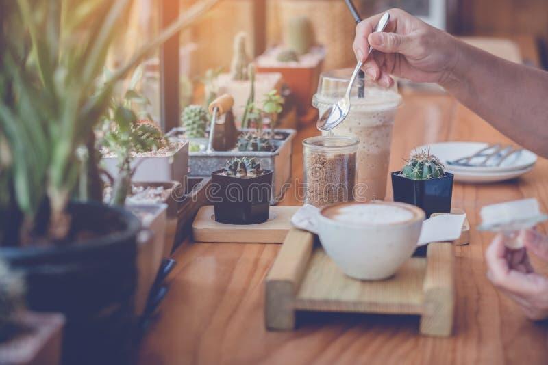 Χύνοντας ζάχαρη γυναικών σε ένα άσπρο φλιτζάνι του καφέ στοκ εικόνα με δικαίωμα ελεύθερης χρήσης
