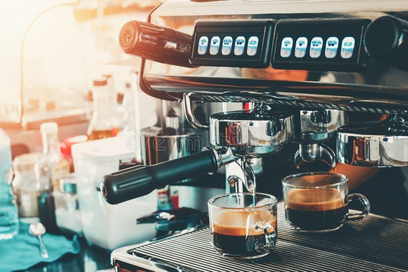 Χύνοντας καφές μηχανών καφέ Espresso σε ένα γυαλί για τις επιλογές καφέ χρήσης στοκ φωτογραφία