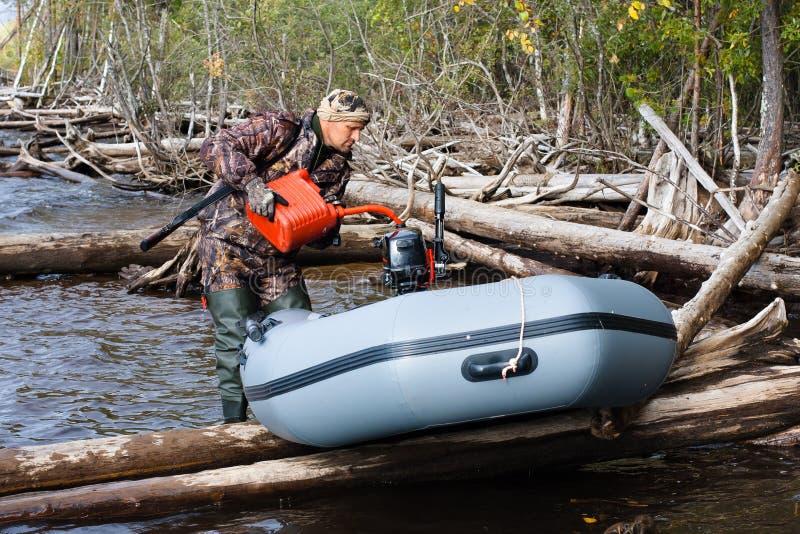 Χύνοντας καύσιμα κυνηγών σε μια δεξαμενή της βάρκας του στοκ εικόνες