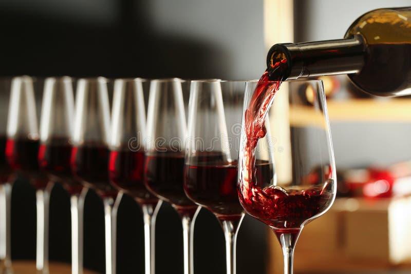 Χύνοντας κρασί από το μπουκάλι στο γυαλί στο κελάρι στοκ εικόνες