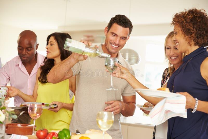 Χύνοντας κρασί ατόμων για το φιλοξενούμενο στο κόμμα γευμάτων στοκ εικόνες
