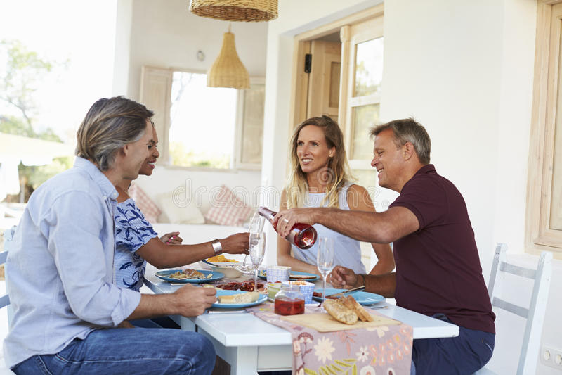 Χύνοντας κρασί οικοδεσποτών για τους φιλοξενουμένους γευμάτων σε έναν πίνακα σε ένα patio στοκ φωτογραφία με δικαίωμα ελεύθερης χρήσης