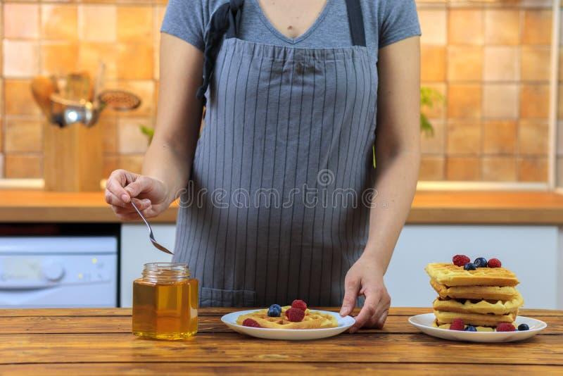 Χύνοντας μέλι γυναικών στις εύγευστες βάφλες με το σμέουρο και τα βακκ στοκ εικόνα