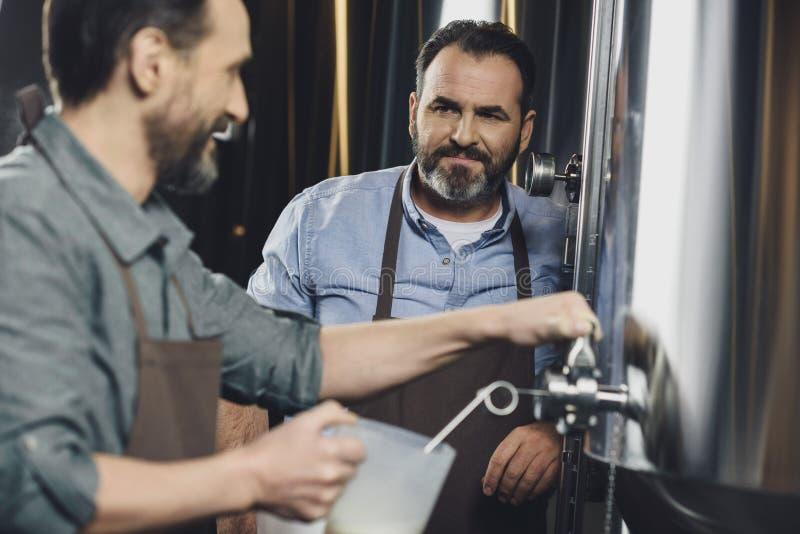 Χύνοντας μπύρα εργαζομένων ζυθοποιείων στοκ φωτογραφίες