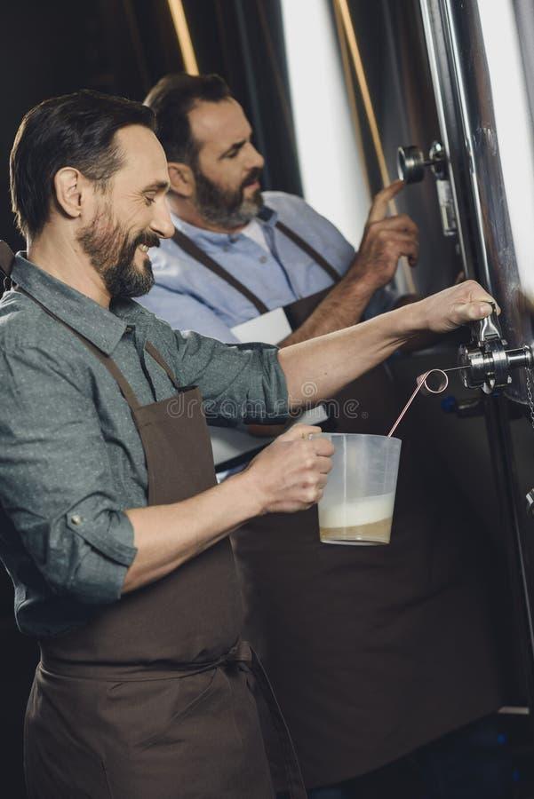 Χύνοντας μπύρα εργαζομένων ζυθοποιείων στοκ εικόνα