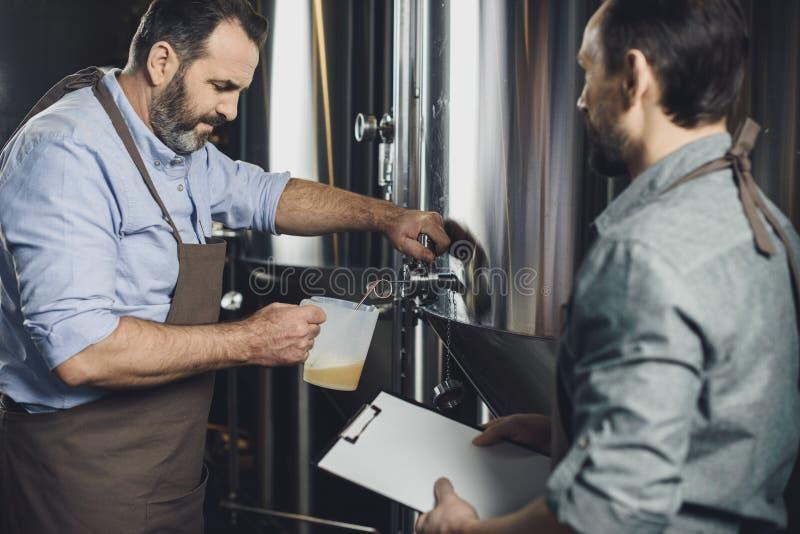 Χύνοντας μπύρα εργαζομένων ζυθοποιείων στοκ εικόνες με δικαίωμα ελεύθερης χρήσης
